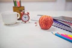 Di nuovo alla mela ed al libro rossi di concetto della scuola sulla tavola bianca Immagini Stock