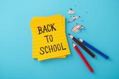 Di nuovo alla parola della scuola sulla nota gialla con le matite di colore fotografia stock