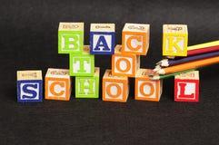 Di nuovo alla scuola compitata con i blocchetti di alfabeto Fotografie Stock