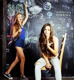 Di nuovo alla scuola dopo le vacanze estive, due ragazze teenager in aula con la lavagna dipinta Fotografia Stock