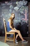 Di nuovo alla scuola dopo le vacanze estive, due ragazze teenager in aula con la lavagna dipinta insieme Fotografia Stock