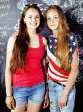 Di nuovo alla scuola dopo le vacanze estive, due ragazze teenager in aula con la lavagna dipinta insieme fotografie stock libere da diritti