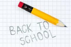 Di nuovo alla scuola scritta su una carta quadrata Immagini Stock