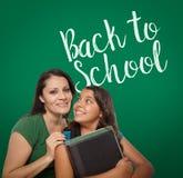 Di nuovo alla scuola scritta sul bordo di gesso dietro la mamma ispana fiera fotografia stock libera da diritti