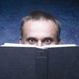 Di nuovo alla scuola scritta sul libro nero Uomo maturo dietro il libro su fondo blu Fotografie Stock Libere da Diritti