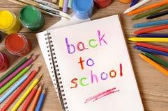 Di nuovo alla scuola scritta in un libro aperto, scrittorio, matite, aula immagini stock libere da diritti
