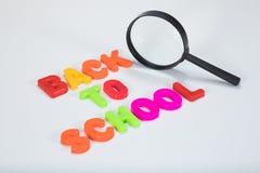 Di nuovo alle lettere ed alla lente d'ingrandimento della scuola Immagini Stock