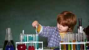 Di nuovo a scuola ed a tempo felice il bambino sta imparando nella classe su fondo della lavagna Bambino dalla scuola primaria Im archivi video