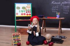 Di nuovo a scuola! La scolara si siede su una lezione con un orologio in sue mani Concetto del banco Sulla lavagna nella lingua u fotografia stock libera da diritti