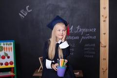 Di nuovo a scuola! Ragazza allegra a scuola con le matite vicino alla lavagna Concetto del banco Sulla lavagna nel langu ucraino fotografia stock