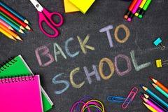 Di nuovo a scuola scritta in gesso contro una lavagna con i rifornimenti di scuola immagini stock libere da diritti