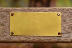 Di piastra metallica dorato in bianco su legno Fotografia Stock Libera da Diritti