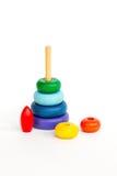 Di piramide di legno colorata multi del giocattolo dei bambini isolata sulla parte posteriore di bianco fotografia stock