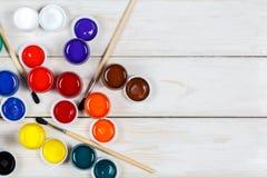 di pittura colorata Multi con le spazzole su un fondo di legno bianco Fotografia Stock