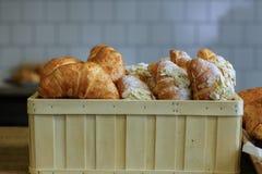 Di recente croissant al forno dorati in un canestro della paglia su una parte posteriore grigia fotografie stock libere da diritti