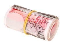 Di sterlina rotolato sulle banconote Fotografie Stock Libere da Diritti