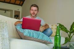 Di stile di vita ritratto all'interno di giovane uomo felice attraente e bello che si siede a casa lo strato del sofà che funzion fotografia stock