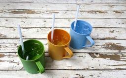 Di tazze colorate multi di plastica su un vecchio legno del fondo Fotografia Stock