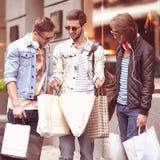 Di tre giovani di modo passeggiata maschio di acquisto del negozio metraseksualy Fotografia Stock