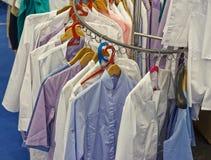 di vestiti colorati Multi che appendono nel guardaroba degli ufficiali sanitari Fotografia Stock