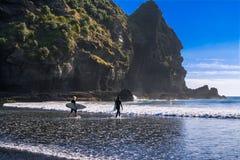 Dia bonito na praia de Piha Surfistas novos que dirigem na água fotografia de stock royalty free