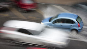 Dia chuvoso na cidade: Conduzir carros na rua bateu pelo hea Imagens de Stock
