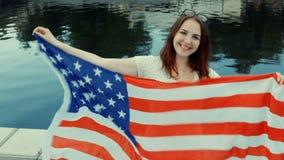 Dia da Independência dos E.U., o quarto de julho Moça bonita no estilo ocasional que sorri com a bandeira americana em suas mãos video estoque
