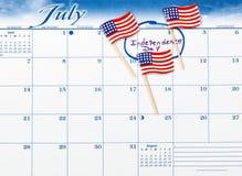 Dia da Independência marcado no calendário com as bandeiras pequenas do Estados Unidos fotografia de stock