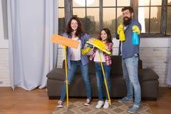 Dia da limpeza Paizinho e filha da mamã da família com fontes de limpeza na sala de visitas Nós amamos a limpeza e a limpeza fotografia de stock royalty free