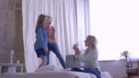 Dia da mãe, as meninas engraçadas de idades diferentes cantam e têm o divertimento na cama para a mamã na sala em casa no tempo d