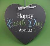 Dia da Terra o 22 de abril feliz, cumprimento do sinal da mensagem em um coração deu forma ao quadro-negro Fotos de Stock Royalty Free