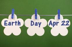 Dia da Terra, o 22 de abril, o cumprimento da mensagem escrito através da flor branca carda a suspensão dos Pegs em uma linha Imagens de Stock Royalty Free