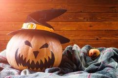 Dia das Bruxas, abóbora alaranjada má e maçã em um fundo de madeira, Foto de Stock