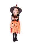 Dia das Bruxas: A bruxa da menina guarda para fora a cubeta da abóbora para deleites fotos de stock