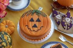 Dia das Bruxas decorou o bolo e o pão-de-espécie serviu na placa cerâmica imagens de stock royalty free
