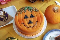 Dia das Bruxas decorou o bolo e o pão-de-espécie serviu na placa cerâmica imagem de stock royalty free