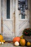Dia das Bruxas decorou a porta da rua com vário tamanho e abóboras e esqueletos da forma Front Porch decorou para Dia das Bruxas fotografia de stock