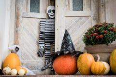 Dia das Bruxas decorou a porta da rua com vário tamanho e abóboras e esqueletos da forma Front Porch decorou para Dia das Bruxas fotografia de stock royalty free