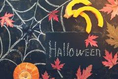 Dia das Bruxas, fatia da abóbora, aranha, folhas de bordo vermelhas, Web de aranha tiradas no giz em um fundo rústico escuro Quad imagens de stock royalty free