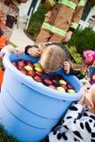 Dia das Bruxas: Menina que sacode-se para maçãs Imagem de Stock Royalty Free