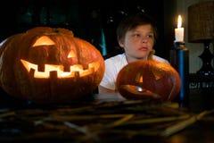 Dia das Bruxas - menino pensativo na frente da abóbora de incandescência Fotografia de Stock