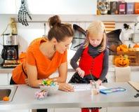 Dia das Bruxas vestiu a Jack-O-lanterna do desenho da menina e da mãe Foto de Stock Royalty Free