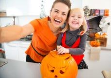 Dia das Bruxas vestiu a menina e a mãe que fazem o selfie na cozinha Fotografia de Stock