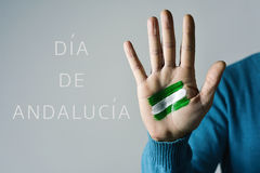 Dia de Andalucia, Day of Andalusia in Spanish. The text Dia de Andalucia, Day of Andalusia in Spanish, and the flag of Andalusia, Spain, painted in the palm of a Royalty Free Stock Images