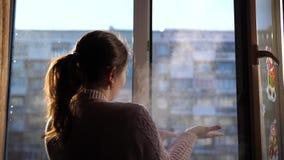 Dia de inverno frio A menina abre a janela e respira no ar gelado vídeos de arquivo
