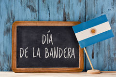 Dia de la Bandera, Flag Day of Argentina. The text Dia de la Bandera, Flag Day written in Spanish in a chalkboard, and a flag of Argentina, on a rustic wooden Royalty Free Stock Image