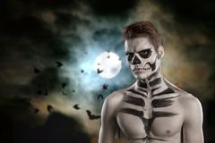 Dia de los Muerto Costume - Day of the dead is a mexican holiday. Here is a man with skull face. Against a cloud and a full moon. Halloween stock images