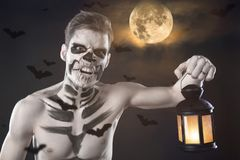Dia de los Muerto Costume - Day of the dead is a mexican holiday. Here is a man with skull face and blurry background. Man with Halloween make up and lantern royalty free stock photos