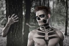 Dia de los Muerto Costume - Day of the dead is a mexican holiday. Here is a man with skull face. Against the background of a terrible forest and zombies royalty free stock image