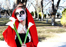 Dia De Los Muertos. Woman in Dia De Los Muertos, Day of the Dead, makeup in cemetary Royalty Free Stock Photo